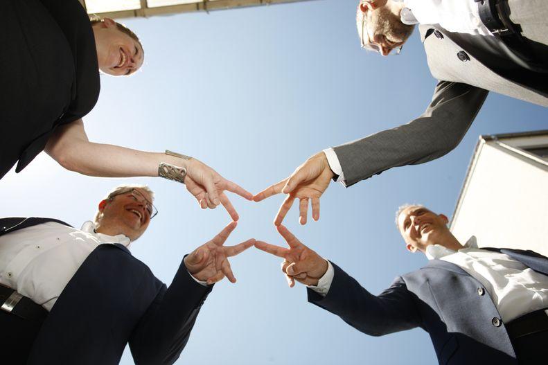Personen die sich gemeinsam die Hände reichen
