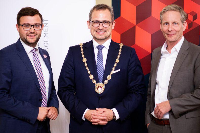 Drei Männer stehen und lächeln