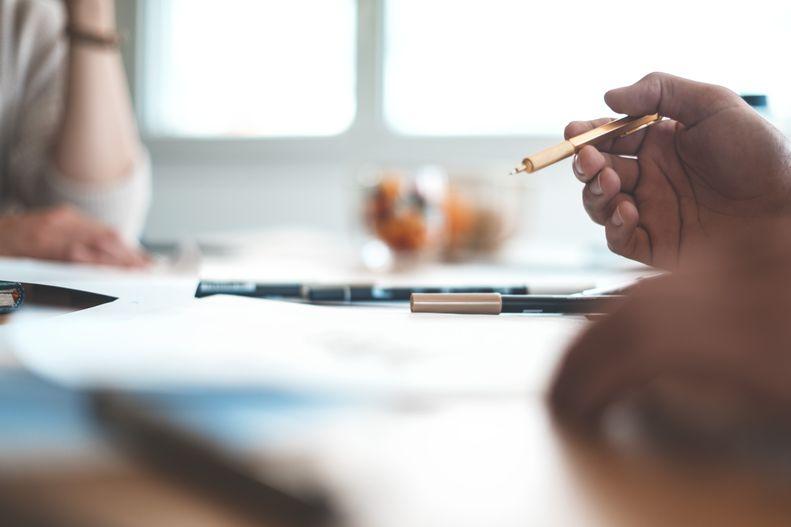 Ein Konferenztisch mit Unterlagen und Stiften. Im Hintergrund ist ein Fenster, rechts sitzt ein Mensch in einem weißen Pullover. Rechts sieht man zwei Hände, eine Hand ist im Fokus und hält einen Stift.