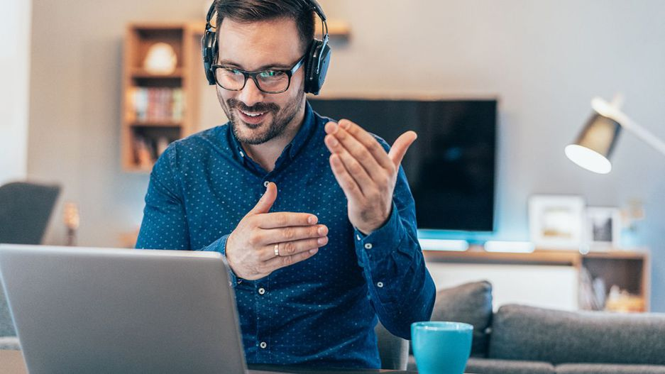 Gestikulierender Mann vor seinem Laptop im Home-Office