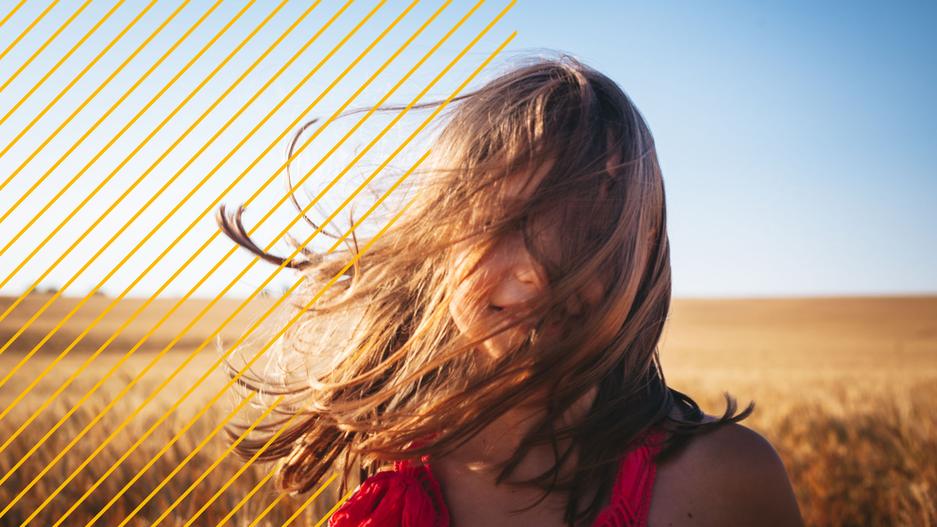 Mädchen mit wehenden Haaren in der Sonne