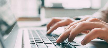 Männliche Hände tippen auf einer Tastatur.
