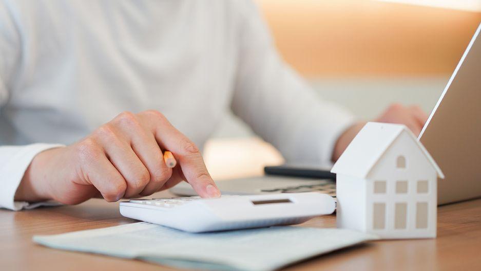 Auf dem Bild ist ein Mann an seinem Schreibtisch zu sehen, der etwas in einen Taschenrechner eingiebt.