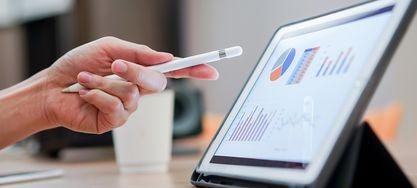 Ein Tablet steht rechts auf dem Tisch. Eine männliche Hand zeigt mit einem Stift auf die Infografiken auf dem Tabletscreen.
