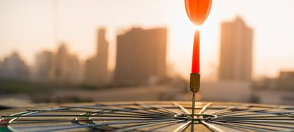Roter Pfeil Pfeil trifft Dartscheibe mit Stadt und Sonnenuntergang