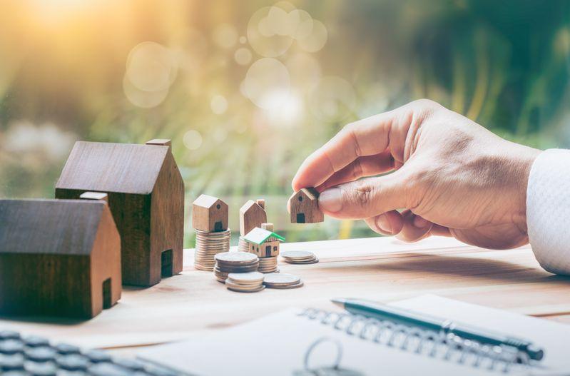 Hand platziert kleine Häuser auf Münzen