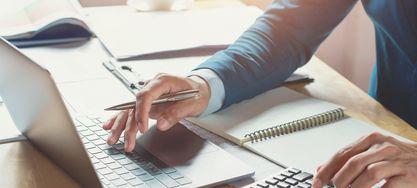 Männliche Hände arbeiten auf einem Laptop und einem Taschenrechner.