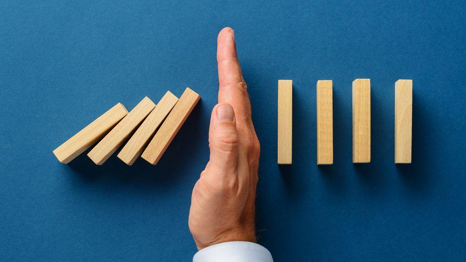 Hand zwischen Dominosteinen