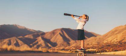 Bild von einem jungen Mädchen, das durch ein Teleskop schaut