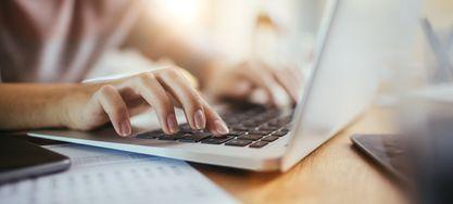 Frau schreibt auf einem Laptop