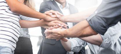 Übereinandergeschlagene Hände für Zusammenarbeit